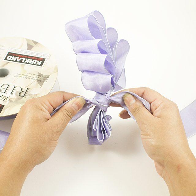 Отрезаем небольшой новый кусочек такой же ленты и завязываем его вокруг хвостика «веера»