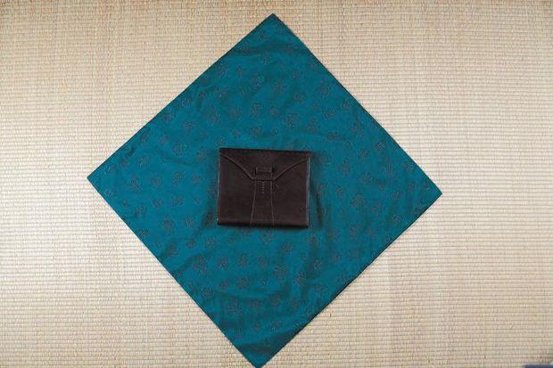 Платок (инструкции по правильному выбору платков боджаги смотрите в начале первой части статьи) кладем ромбом, более темной стороной вверх. В центр, как обычно, горизонтально ставим коробку с подарком