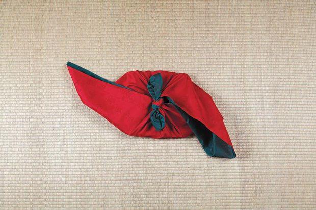 Верхний и нижний углы платка собираем сверху над коробкой и связываем вместе по центру подарка двумя(!) обычными узлами