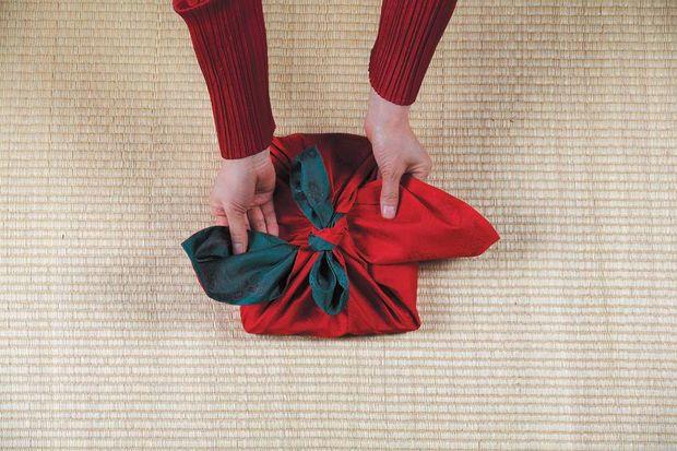 Два боковых уголка платка тоже поднимаем вверх и протискиваем их на противоположные стороны под двойным узлом на подарке