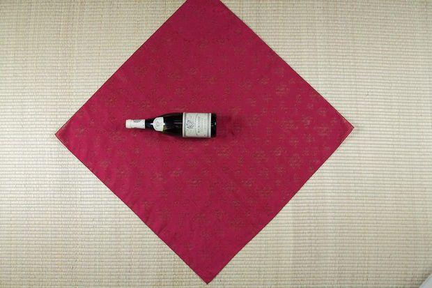 Теперь платок кладем ромбом, бутылку размещаем сверху плашмя так, чтобы ее донышко было в центре платка, а горлышко указывало на левый угол ромба платка.