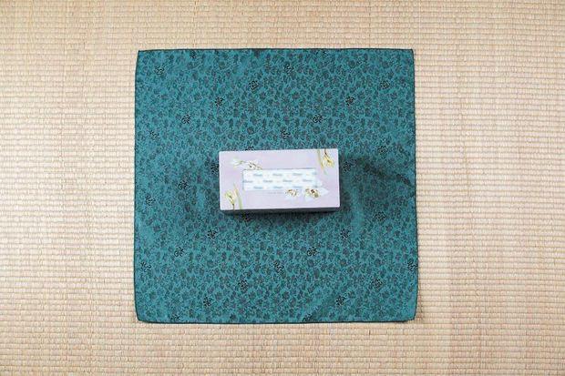 Платок кладем квадратом, в центр него ставим коробку горизонтально, т. е. чтобы более короткие стороны коробки смотрели вправо и влево, а не вверх и вниз