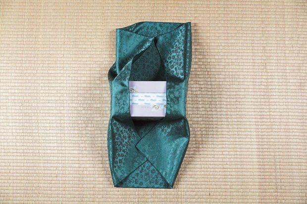 Правую и левую стороны платка поднимаем наверх и кладем края боджаги на коробку сверху