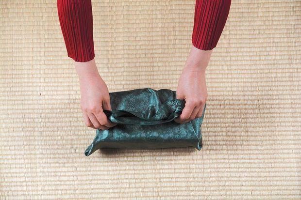 Над подарком ровно вертикально вверх совмещаем два последних сложенных края