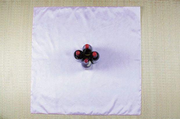 кладем большой квадратный платок ровно перед собой, при этом 4 бутылки ставим в самый центр, но уже ромбом по отношению к нижнему краю платка