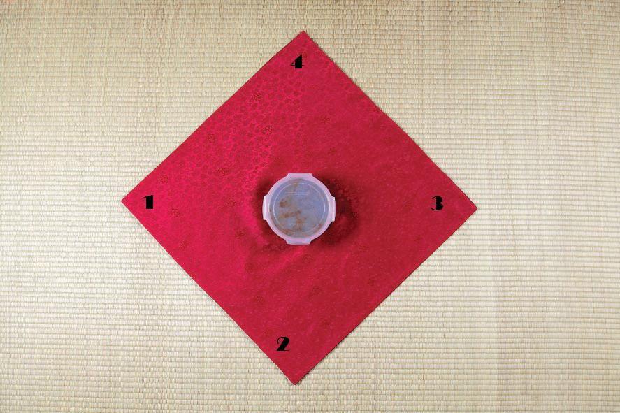 Ромбом (один угол смотрит на вас) кладем платок изнаночной стороной вверх, в центр ставим подарок