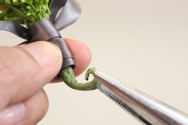 Из кончика ножки-основы бутоньерки сделайте небольшой завиток при помощи плоскогубцев