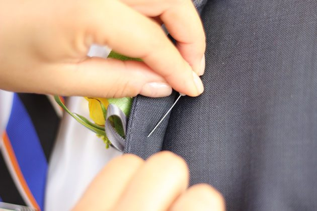 Прикалывают бутоньерку всегда слева. К лацкану пиджака следующим образом (булавка проходит через сердцевину ножки-основы по длине).