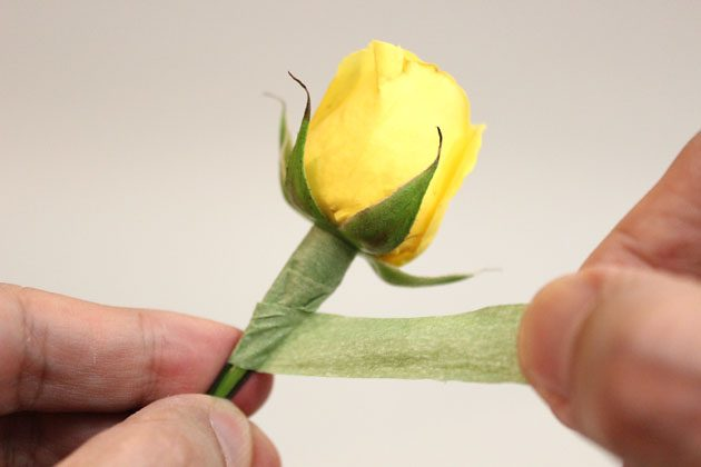 под головкой цветка начинайте по плотной спирали оборачивать проволоку со стеблем флористической лентой