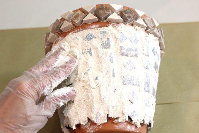 Надевайте резиновые перчатки и распределите уже замешанный желтоватый цемент прямо поверх плиток и между ними