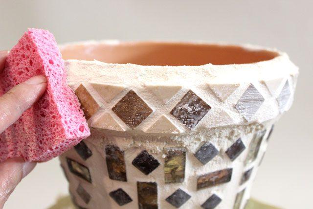 Стираем пальцем лишний цемент, отмываем плитку губкой