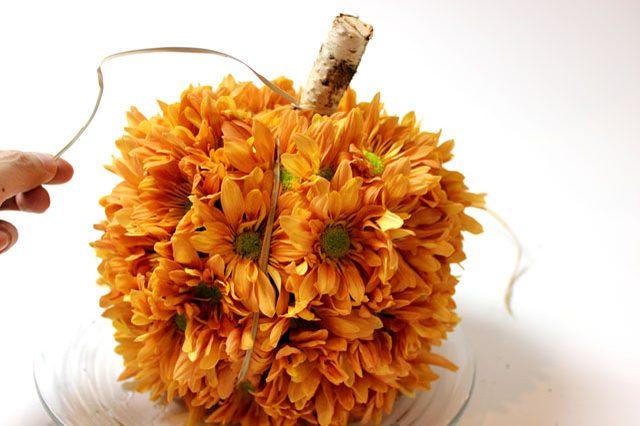 Поверх цветов оборачиваем рафию, имитируя вертикальные желобки-секции на поверхности настоящей тыквы