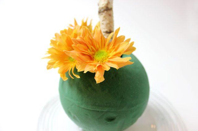 Вставляем цветы в шар из флористической губки: закрыть его поверхность они должны полностью
