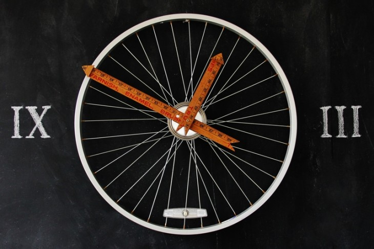 часы из велосипедного колеса и часового механизма со стрелками из линеек