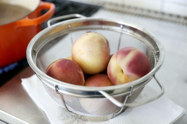 Вытаскиваем персики, переворачивая кастрюлю в большой заранее подготовленный дуршлаг в раковине