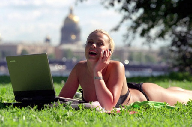 девушка в купальнике загорает на травке и одновременно работает за ноутбуком