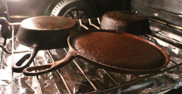 На нижнем поддоне духовки закрепите листы фольги, положите чугунные сковороды вверх дном на сетку