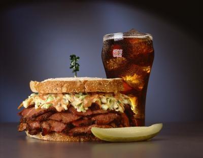 Coca-Cola в стакане бутерброд бургер и долька соленого огруца