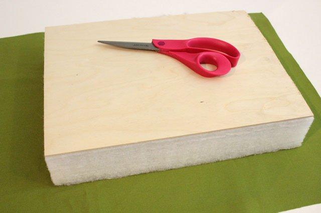 Расстилаем на ровной поверхности ткань, на нее по центру кладем поролон, сверху на поролон ровно кладем фанеру