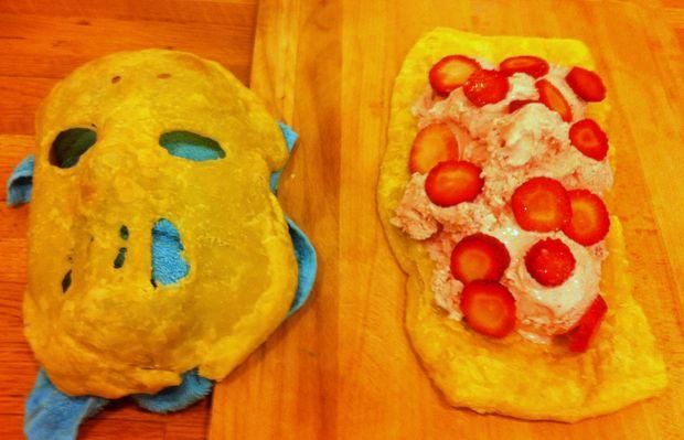 Внутрь торта-пирога, имитируя изуродованное лицо, помещаем крем розового цвета (или мороженое) и процеженное красное варенье, джем или сладкий красный соус. Можно добавить резаные дольками красные фрукты и ягоды.
