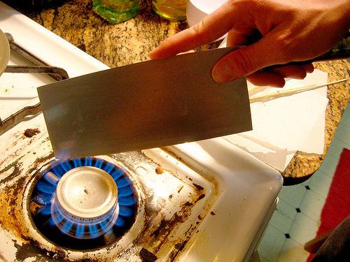 Берем большой тесак и нагреваем его непосредственно в огне – над плитой, свечкой или даже зажигалкой