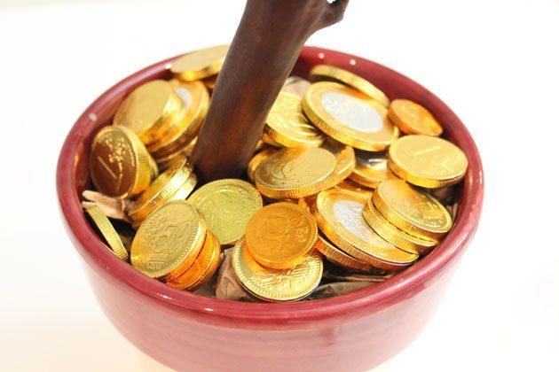 Поверх бумаги положите шоколадные или азиатские монетки удачи