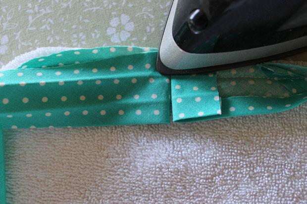 Сложите оставшиеся свободными кончики ленты вместе и там, где они начнут соприкасаться, согните кончики по вертикали направо и налево соответственно