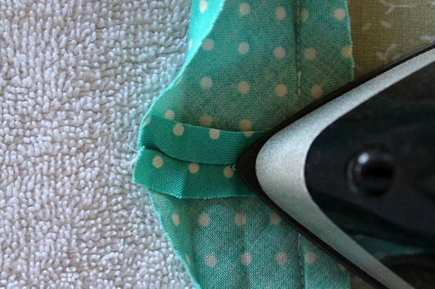 Обрежьте лишнюю ткань, раскройте короткие кончики и в таком положении прогладьте ленту утюгом