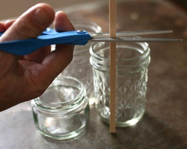 Примеряйте палочки из бальзы по очереди ко всем выбранным баночкам для свечей и обрезайте рейки до индивидуальных фитилей длиной на 2,5 см выше края