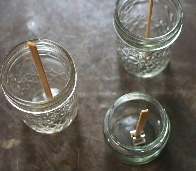 Используя восковой клей, по одному приклейте с нажимом основания с фитилями ко дну каждой баночки по центру