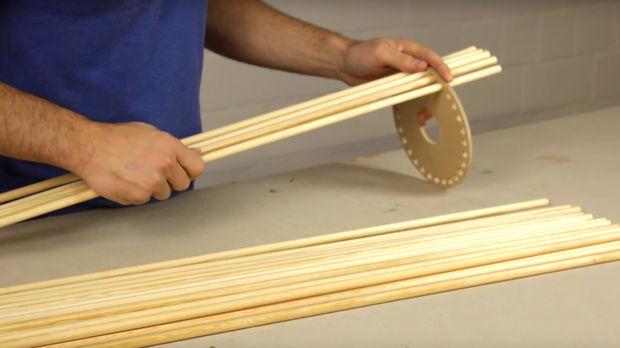 Далее в малые отверстия по периметру той же детали вставляем круглые деревянные палочки так, чтобы над доской оставались кончики палок длиной 10 см
