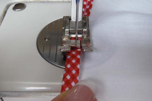 Перегните сдвоенную матерчатую ленту через обрезанный край и шов