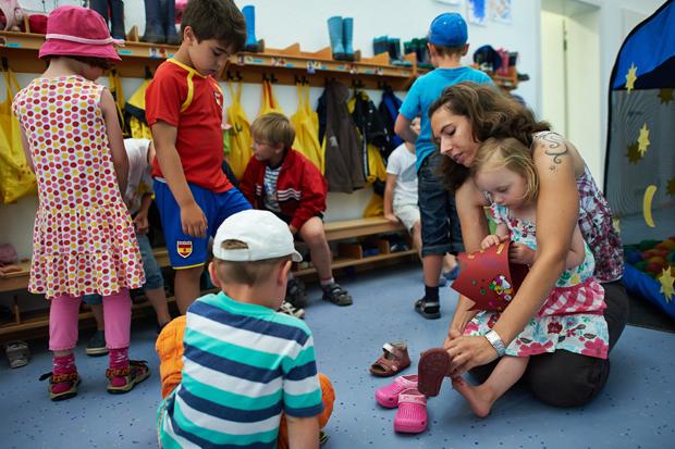 помогай другим: мама помогает девочке в школе одеть ботиночки