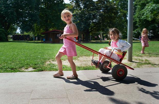 старшая девочка катает на повозке младшую