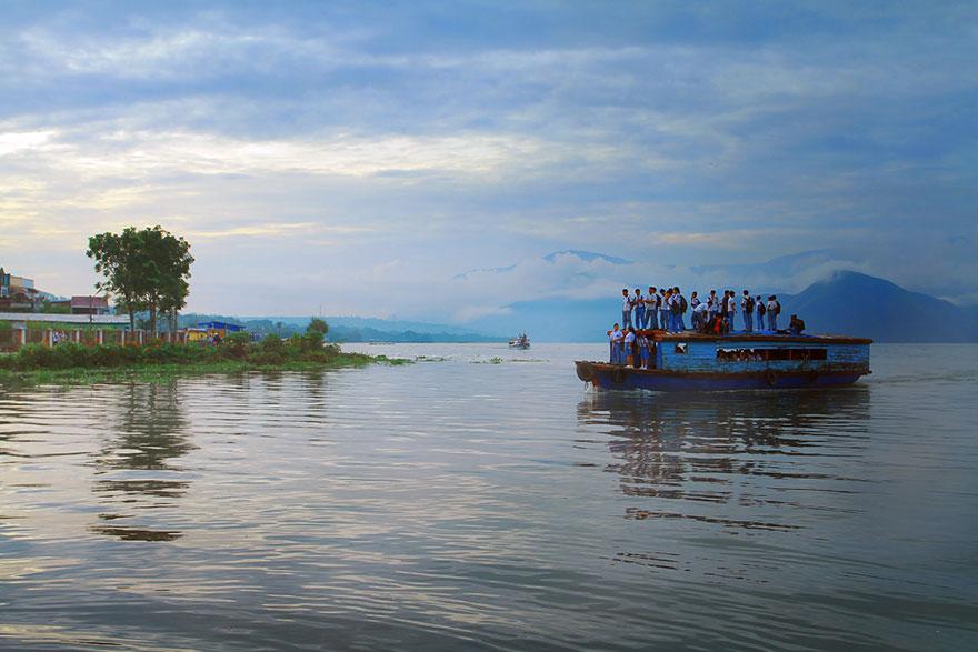 дети плывут сверху на крытом катере - Pangururan, Индонезия