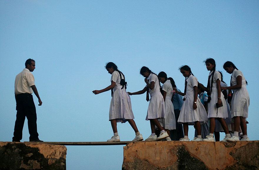 школьницы, пересекающие по незакрепленной доске разрыв в стене форта Галле (16-й век) – Шри-Ланка