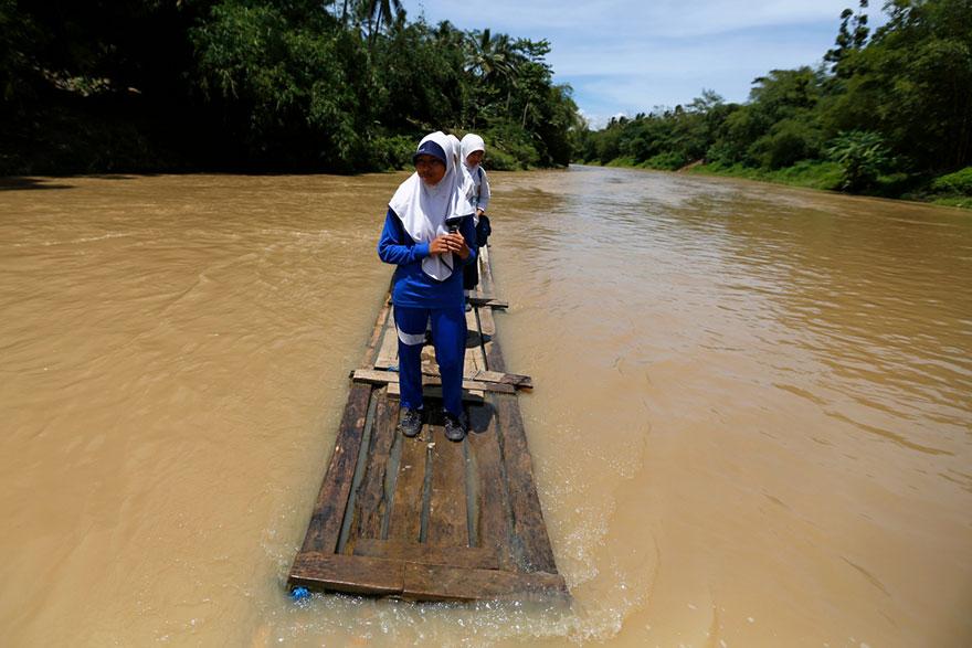 школьницы пересекают реку Ciherang на самодельном бамбуковом плоте – деревня Cilangkap, Индонезия