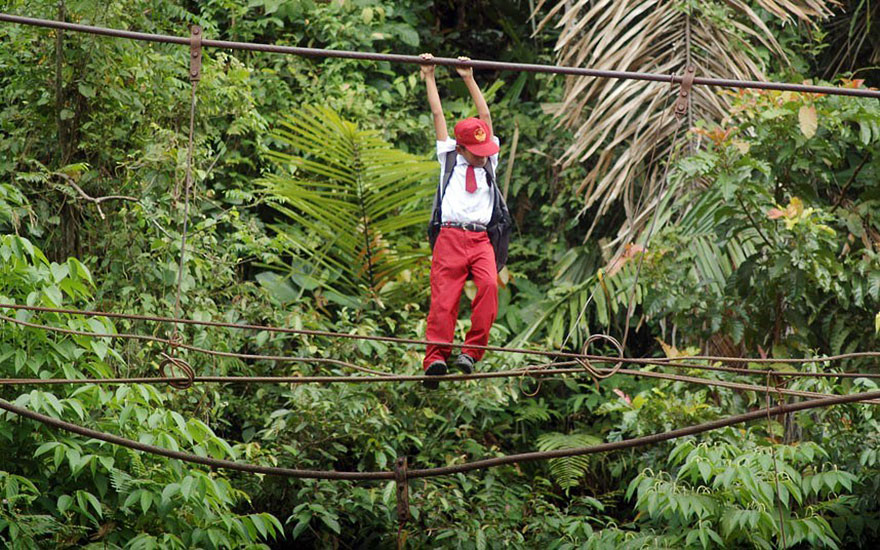 ученики, переходящие по канатной дороге более чем в 9-ти м над водой - Паданг, Суматра, Индонезия