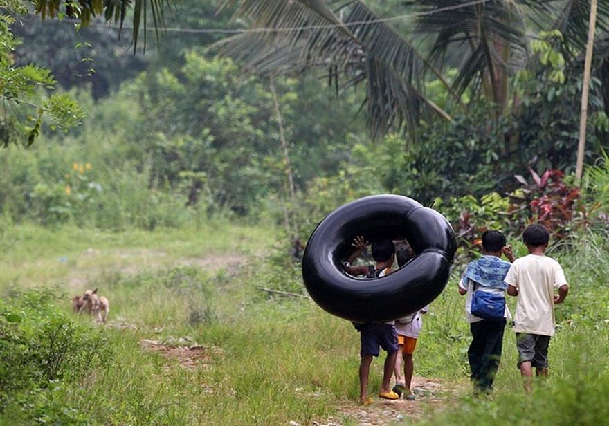 ученики младших классов, пересекающие реку на накачаной камере от большого колеса - провинция Ризал, Филиппины