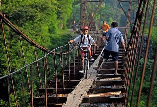 дети, пересекающие старый, ржавый акведук, проложенный деревянными мостками – также Индонезия, Ява