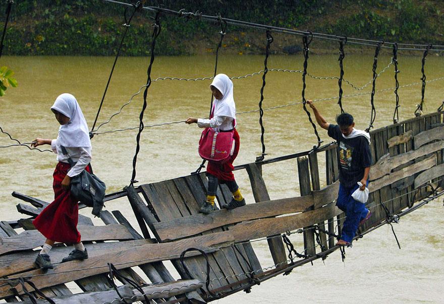 ученики, пересекающие поврежденный подвесной мост - Lebak, Индонезия