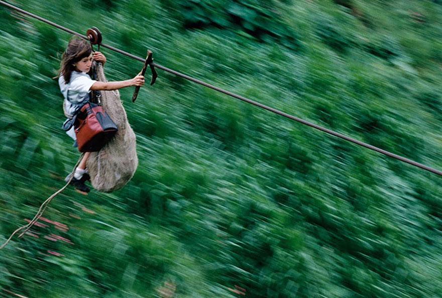 девочки и мальчики, проносящиеся под километр на стальном тросе на высоте 400 метров, чтобы пересечь реку Рио-Негро, Колумбия