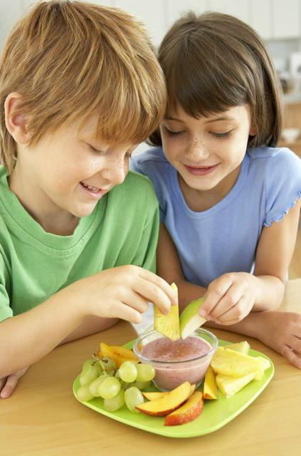 дети макают кусочки фруктов в йогурт