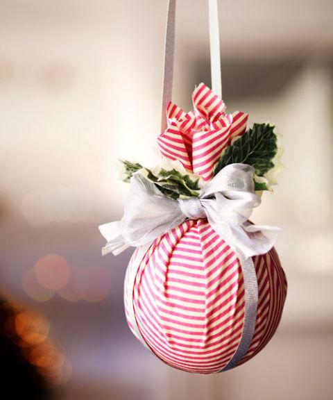 Один из самых быстрых и простых способов украсить непонравившийся новогодний шар, придать ему шарма и индивидуальности – обернуть его в ткань по типу мешочка, а затем добавить сверху покупные рождественско-новогодние веточки