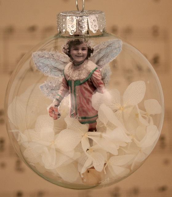 В прозрачном елочном шаре отделанная блестками фотография девочки