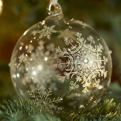 Снежинка, нарисованная от руки на прозрачном елочном шаре