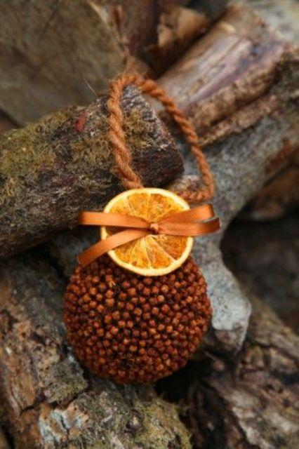 Ароматический елочный шар, оклеенный сухими венчиками гвоздики и украшенный настоящей сушеной долькой апельсина