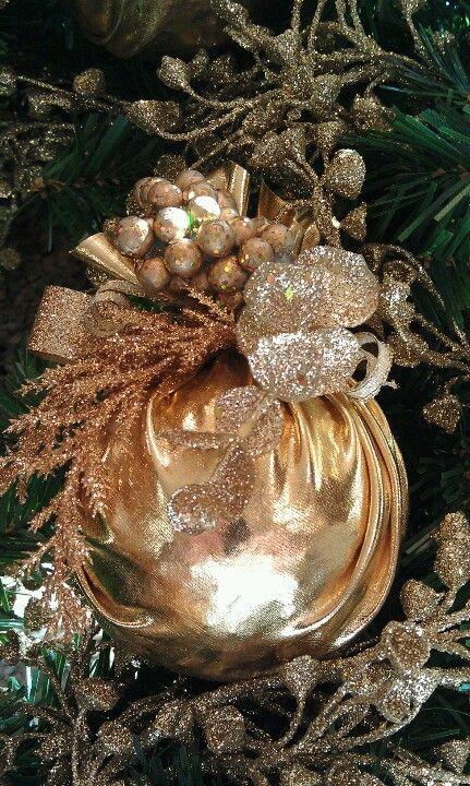 Один из самых быстрых и простых способов украсить непонравившийся новогодний шар, придать ему шарма и индивидуальности – обернуть его в золотую ткань на манер мешочка, а затем добавить сверху покупные рождественско-новогодние веточки