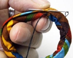 Из цветастой ткани, желательно с современным принтом, сшиваем небольшую трубу, выворачиваем ее на лицевую, набиваем ватой, сшиваем в круг