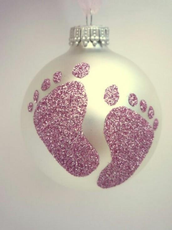 Обведите ножку вашего новорожденного малыша на бумаге. Переведите методом карбонирования изображение на елочный шар, а дальше дело только за клеем и блестками